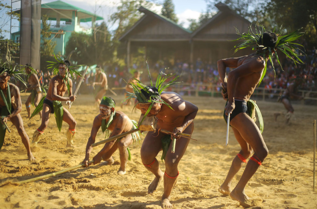 The images shows a mock war drill in  Hornbill Festival by Naga People